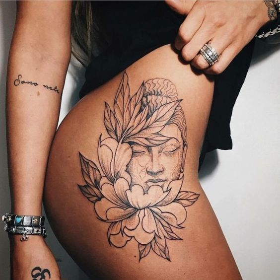 buddha tattoo and flower on thigh