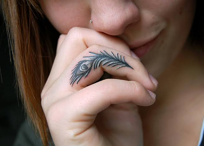 feather tattoo on side finger